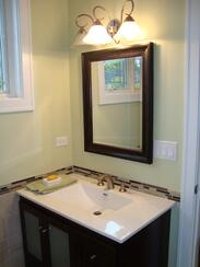 Small bathroom with single vanity and a tile half wall.