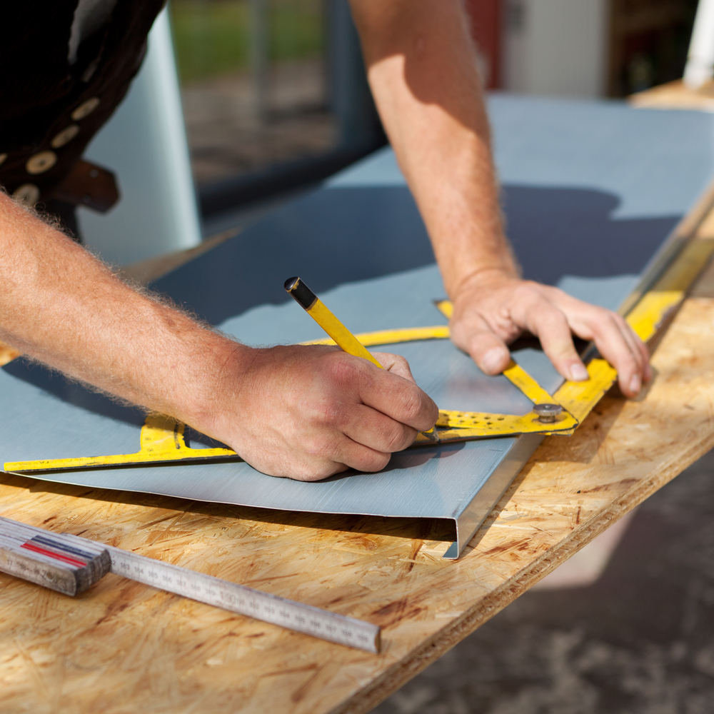 Roofer working with a protractor to make markings on a metal sheet-1